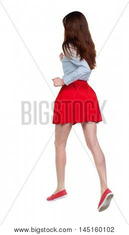 side view of running woman. beautiful girl in motion. Long-haired brunette in red skirt high jumps.
