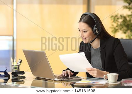 Freelance operator working online with a laptop and headsets and holding a document at office