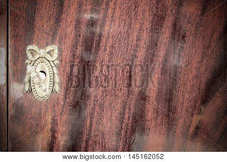 Vintage keyhole with key on vintage wooden cabinet