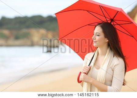 Portrait of a longing woman thinking and looking at horizon under a red umbrella on the beach with the sea in the background