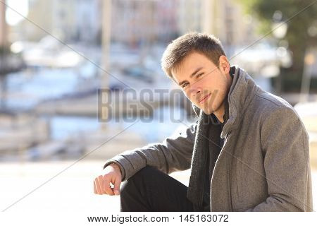 Portrait of a young handsome man wearing a grey jacket in winter sitting in the street of a port