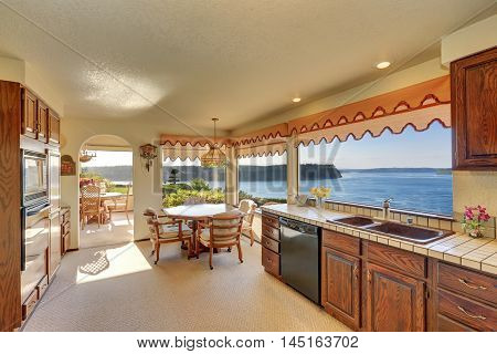 Kitchen And Dining Room Interior With Carpet Flooring And Arched Entry