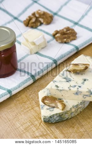 Cheese roquefort with nuts and jam on the towel