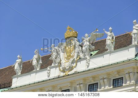 Statues on the roof of Hofburg Palace against the blue sky at sunny midday