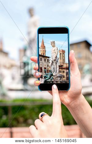 Photographing with mobile phone fountain of Neptune in Florence old town in Italy