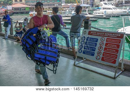Kota Kinabalu,Sabah-Aug 30,2016:Tourist guide of Jesselton Point Terminal preparing distribute tourist with the life jacket before heading to the islands in Tunku Abdul Rahman Marine Park nearby.