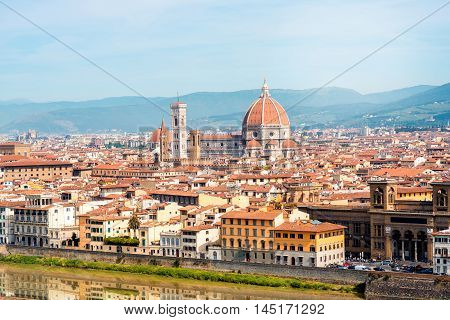 Florence aerial cityscape view from Michelangelo square on the old town with famous cathedral church and river in Italy