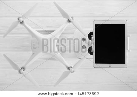 concept quadrocopter, tablet and remote control on a white wooden background