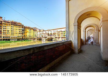 Cityscape view on famous Ponte Vecchio bridge with arch corridor in Florence