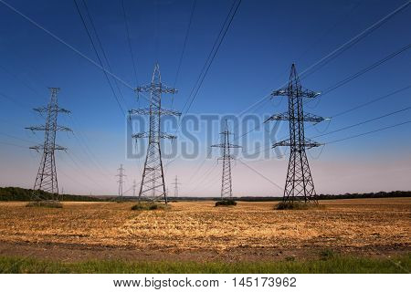 Rows of transmission towers and power lines in the field in the countryside