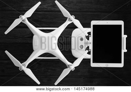 concept drone, tablet and remote control on a black wooden background