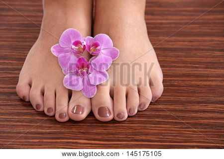 Female feet with brown pedicure and orchid on wooden background