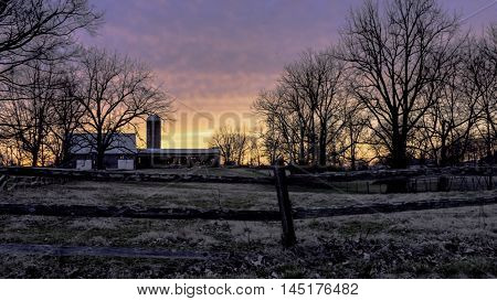 Sunset in rural Kentucky over a dairy farm with split rail fence in the foreground