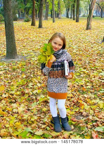 little girl with yellow leaves and book stands in the park