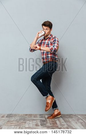 Wondered young man drinking takeaway coffee and looking at wristwatch over grey background