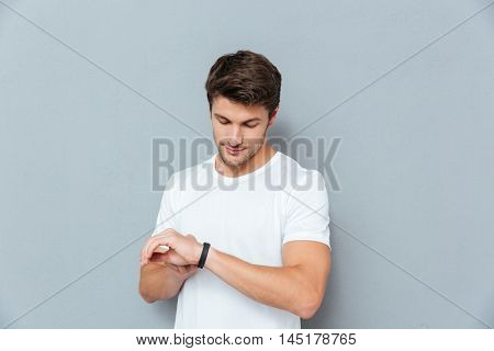Serious young man standing and checking fitness tracker over grey background
