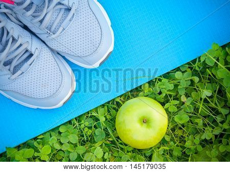 Sports shoes sneakers on yoga mat and apple on fresh green grass. Sports in the open air. top view
