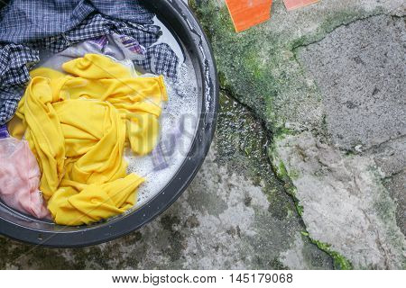 Soak dirty clothes in the sink black for clean Thailand washing clothes style ancient :Close up select focus with shallow depth of field.
