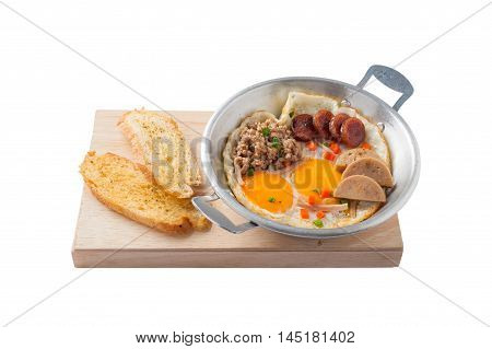 Front view of Vietnamese style pan-freid egg with Chinese sausage minced pork Vietnamese sausage in metal pan on wood plate with toast isolated on white background
