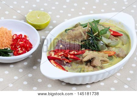 Green chicken curry in coconut milk served with side dish as minced dried shrimp,sliced red chili,sliced kaffir lime leaves and green lemon.on gray.Selective focus.