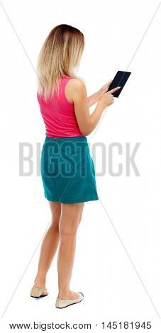 back view of standing young beautiful woman using a mobile phone or tablet computer. Isolated over white background. Blonde in a red sweater and green skirt flips through pages with your finger on the