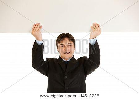 Smiling modern businessman holding blank billboard over head