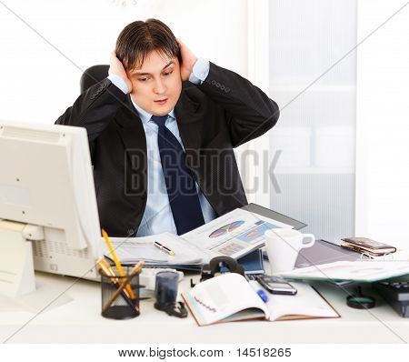 Stressful young businessman sitting at office desk being overloaded with loads of work