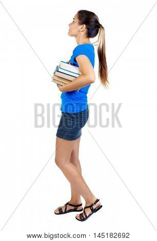 Girl comes with stack of books. side view. girl in a short skirt and a blue T-shirt goes to the side with a stack of books.