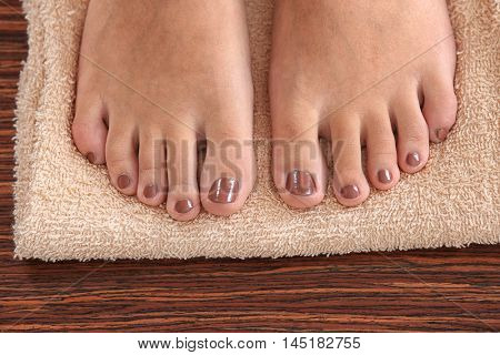 Female feet with brown pedicure on towel, closeup