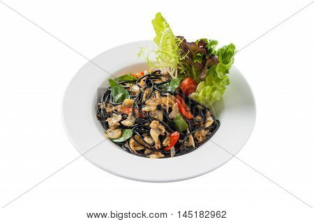 Front view of Italian and Thai fusion food style spicy black pasta with clams garnished with red chili and vegetables in ceramic dish isolated on white bckground