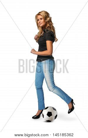 Attractive blonde woman kicks a football in a studio.