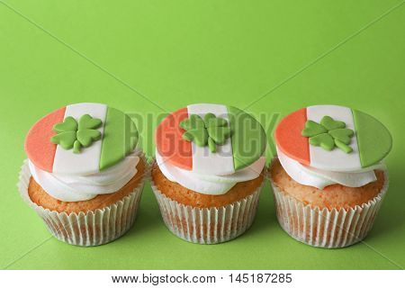 Tasty cupcakes with clover on green background. Saint Patrics Day concept