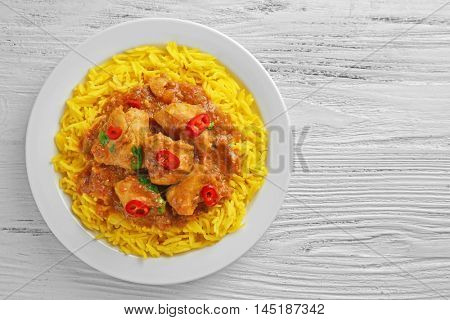Tasty dinner with chicken curry and rice in plate on wooden background