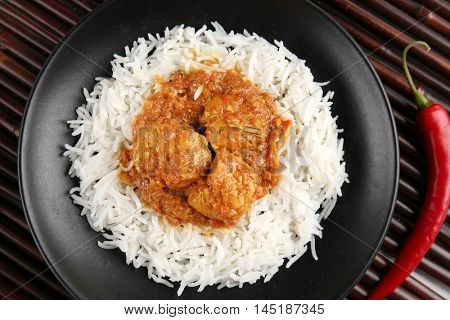 Tasty dinner with chicken curry and rice in plate on bamboo background