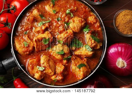Tasty chicken curry in pan and spices, closeup