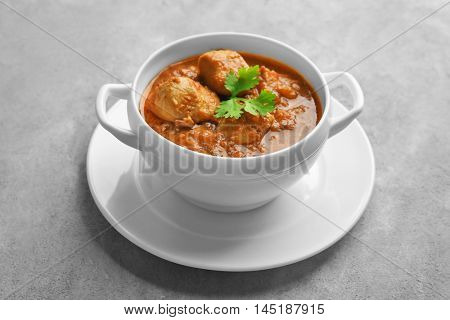Tasty chicken curry in soup plate on grey background