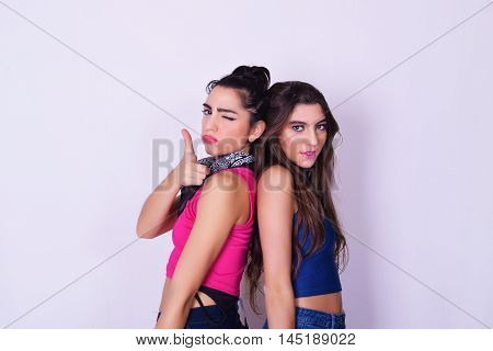 Portrait of two beautiful women posing. Friendship concept. Trendy and stylish friends isolated over grey background.