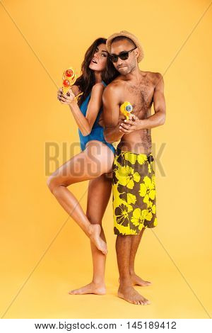 Couple standing back to back ready for a water pistol duel isolated on the orange background