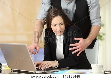 Harassment with a boss touching the arm to his secretary who is sitting in his workplace at office