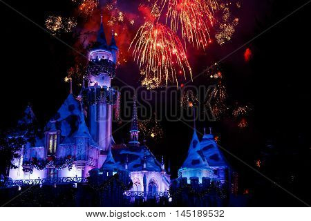 Fireworks in disneyland behind the snowhite house