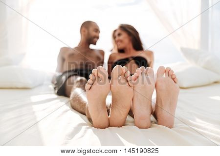 Image of happy multiracial couple laying at the white beach bed outdoors