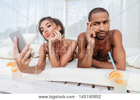 Beautiful girl making selfie with smartphone with displeased african man at the beach