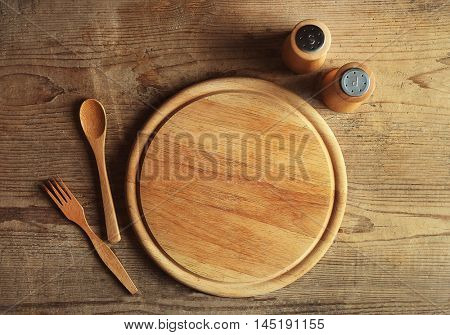 Empty cutting board and kitchen tools on wooden planks background