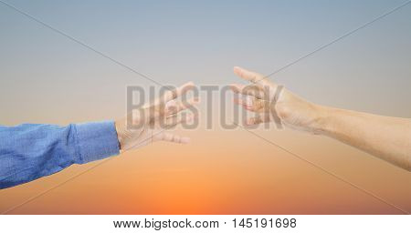 Hands reaching together on sky in sunset background