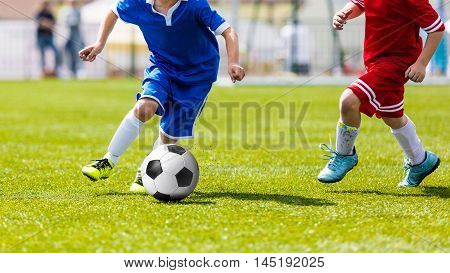 Two young soccer footballers kicking soccer match. Running players in red and blue sports uniforms. Youth soccer teams competing on sports field