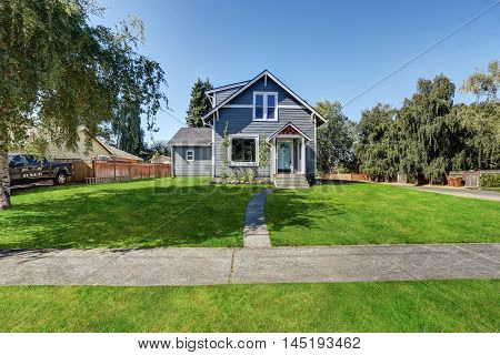Blue Clapboard Siding House With Grass Filled Front Yard.
