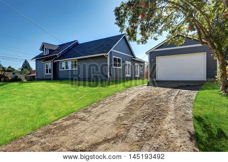Backyard View Of  Blue Siding House With Detached Garage