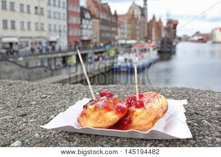 Sheep fried cheese with cranberry sauce. Street food on the embankment in Gdansk. Polish cuisine.