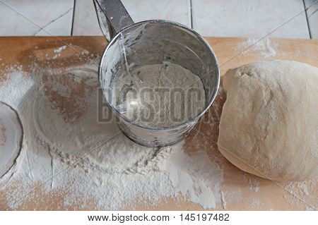 Metal Flour Sifter With Flour And Dough On Wooden Desk