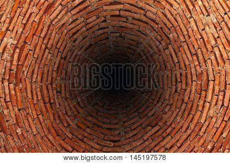Very deep well made of red bricks